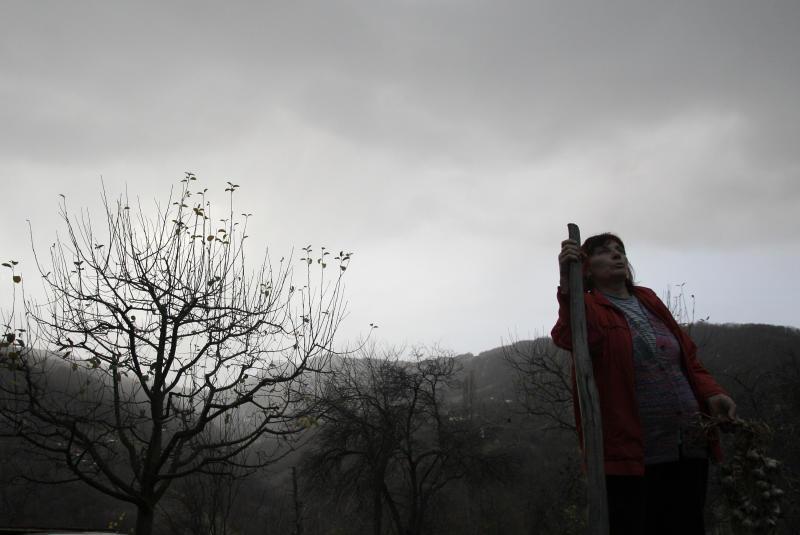 In this Nov. 30, 2012 photo Milka  Prokic is seen at twilight with a garland of garlic and a wooden stake, in the village of Zarozje, near the Serbian town of Bajina Basta. Get your garlic, wooden crosses and stakes ready: a bloodsucking vampire is on the loose.  Or so say villagers in the tiny western Serbian hamlet of Zarozje, nestled between the lush green mountain slopes and spooky thick forests. Rumors that a legendary vampire ghost has returned are spreading panic throughout the town. An official warning telling villagers to put garlic in their pockets and place wooden crosses in each of their rooms, the tools that should keep away the vampires  did nothing but fuel the fear.  (AP Photo/Darko Vojinovic)