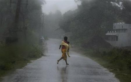A girl runs for shelter in heavy rain brought by Cyclone Phailin in Ichapuram town in Srikakulam district in Andhra Pradesh October 12, 2013. REUTERS/Adnan Abidi