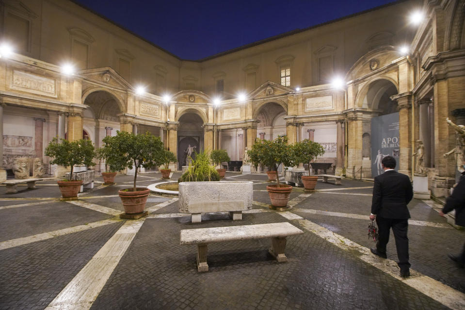 "Gianni Crea, the Vatican Museums chief ""Clavigero"" key-keeper, walks through the octagonal courtyard on his way to open the museum's rooms and sections, the Vatican, Monday, Feb. 1, 2021. Crea is the ""clavigero"" of the Vatican Museums, the chief key-keeper whose job begins each morning at 5 a.m., opening the doors and turning on the lights through 7 kilometers of one of the world's greatest collections of art and antiquities. The Associated Press followed Crea on his rounds the first day the museum reopened to the public, joining him in the underground ""bunker"" where the 2,797 keys to the Vatican treasures are kept in wall safes overnight. (AP Photo/Andrew Medichini)"