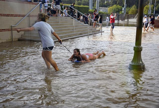 One woman pulls another on a body board through water on the quad of UCLA after flooding from a broken 30-inch water main under nearby Sunset Boulevard inundated a large area of the campus in the Westwood section of Los Angeles, Tuesday, July 29, 2014. The 30-inch (75-centimeter) 93-year-old pipe that broke made a raging river of the street and sent millions of gallons (liters) of water across the school's athletic facilities, including the famed floor of Pauley Pavilion, the neighboring Wooden Center and the Los Angeles Tennis Center, and a pair of parking structures that took the brunt of the damage. (AP Photo/Mike Meadows)