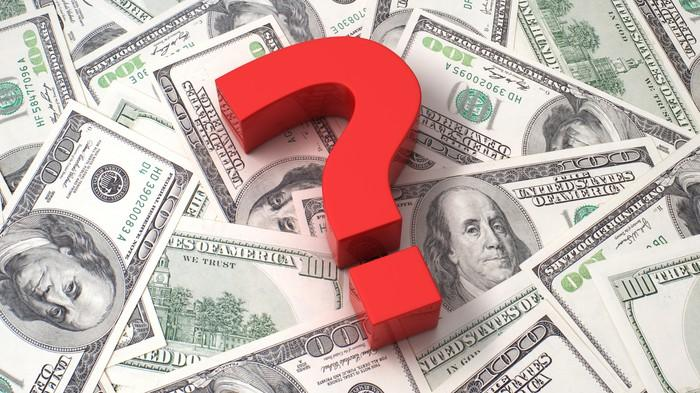 Red question mark on a pile of cash.