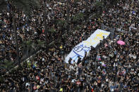 """Tens of thousands of protesters march through the streets with a banner reading """"Hong Kong say No"""" as they continue to protest an extradition bill, Sunday, June 16, 2019, in Hong Kong. Hong Kong residents Sunday continued their massive protest over an unpopular extradition bill that has highlighted the territory's apprehension about relations with mainland China, a week after the crisis brought as many as 1 million into the streets. (AP Photo/Kin Cheung)"""