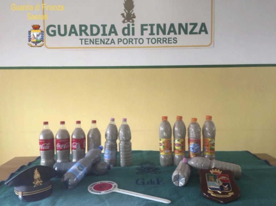 This picture taken on Aug. 16, 2019 by the Finance Police of the Sardinian port of Porto Torres, Italy, shows 14 plastic bottles of sand seized from a French couple in the trunk of the couple's car. The French couple could face up to six years in jail for taking around 40 kg (88.1lbs) of the island's famed white sand from Chia beach, which is protected as a public good. (Italian Finance Police via AP)
