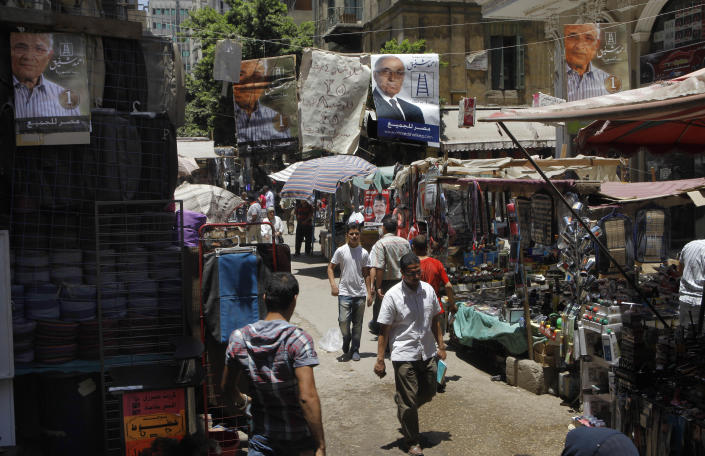 """Campaign posters supporting Egyptian presidential candidate Ahmed Shafiq, the last prime minister of deposed president Hosni Mubarak, hang above a popular market in Cairo, Egypt, Tuesday, June 12, 2012. Arabic on the banners reads: """"Ahmed Shafiq for Egyptian presidency"""", and """"Egypt for all.""""(AP Photo/Amr Nabil)"""