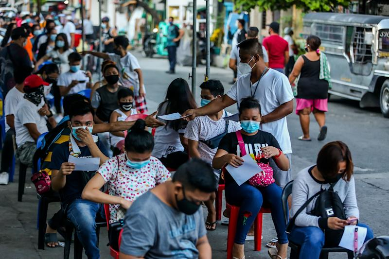 People wearing face masks line up at a walk-in free COVID-19 testing center at Sampaloc Hospital in Manila, the Philippines on July 21, 2020. (Photo: Rouelle Umali/Xinhua via Getty)