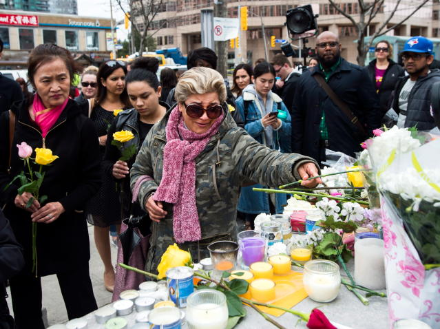 <p>Ozra Kenari, center, places flowers as she cries at a memorial for the victims along Yonge Street the day after a driver drove a van down sidewalks, striking pedestrians in his path, in Toronto, Tuesday, April 24, 2018. (Photo: Nathan Denette/The Canadian Press via AP) </p>