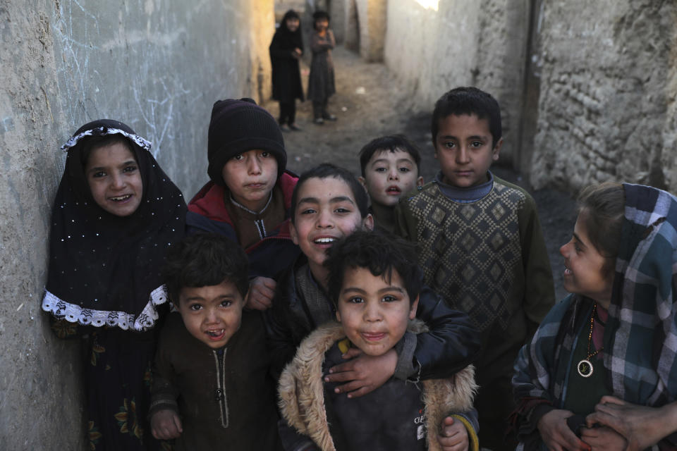 Internally displaced children pose for a photograph outside their temporary home in the city of Kabul, Afghanistan, Wednesday, Dec. 30, 2020. Save the Children has warned that more than 300,000 Afghan children face freezing winter conditions that could lead to illness, in the worst cases death, without proper winter clothing and heating. (AP Photo/Rahmat Gul)
