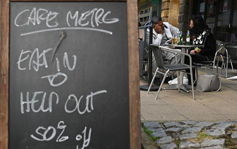 """Diners sit at table near a sign promoting the British Government's """"Eat out to Help out"""" COVID-19 scheme to get consumers spending again, outside a restaurant in Manchester, northwest England on August 3, 2020, - Britain's """"Eat out to Help out"""" scheme began Monday, introduced last month by Chancellor Rishi Sunak to help boost the economy claw its way from a historic decline sparked by the coronavirus crisis. (Photo by Oli SCARFF / AFP) (Photo by OLI SCARFF/AFP via Getty Images) (Photo: OLI SCARFF via Getty Images)"""