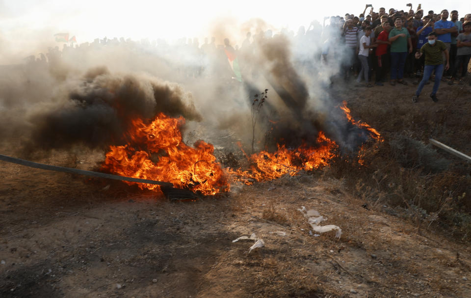 Protestors set fire on a tire near the fence of Gaza Strip border with Israel, during a protest marking the anniversary of a 1969 arson attack at Jerusalem's Al-Aqsa mosque by an Australian tourist later found to be mentally ill, east of Gaza City, Saturday, Aug. 21, 2021. (AP Photo/Adel Hana)