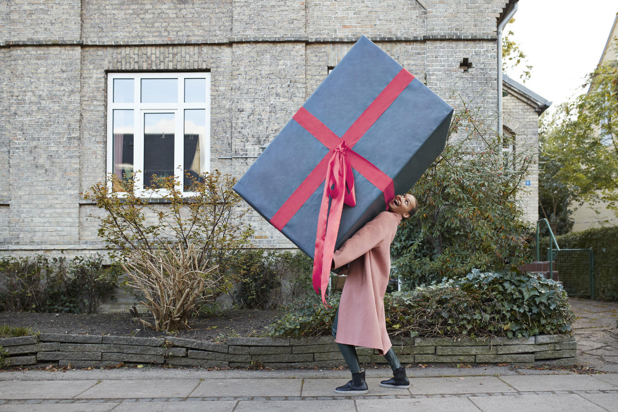 Happy young woman carrying large gift box on footpath
