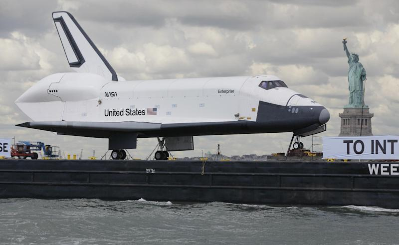 The space shuttle Enterprise passes the Statue of Liberty as it makes the final leg of its journey to its new Manhattan home on the flight deck of the Intrepid Sea, Air & Space Museum, Wednesday, June 6, 2012. The U.S. space agency, NASA, ended its shuttle program last year. (AP Photo/Richard Drew)