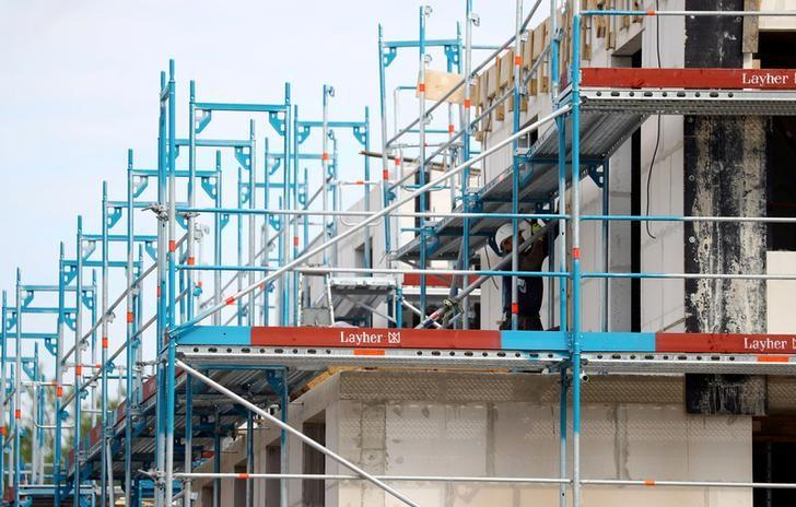 FILE PHOTO: A construction worker adjusts a scaffolding on a construction site for family homes in Hanau near Frankfurt