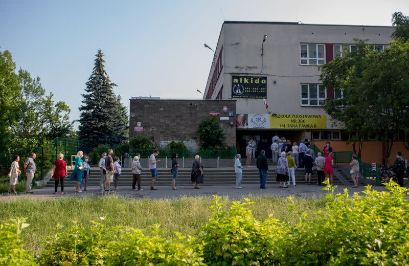 People queue outside a polling station during the presidential election in Warsaw