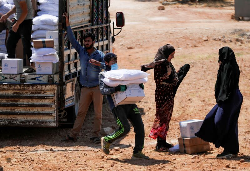 FILE PHOTO: A worker holds bags and a box of humanitarian aid in the opposition-held Idlib