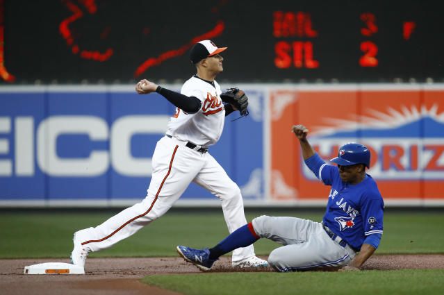 Baltimore Orioles shortstop Manny Machado attempts to turn a double play after forcing out Toronto Blue Jays' Curtis Granderson at second base on a ground ball that was hit by Justin Smoak in the first inning of a baseball game, Wednesday, April 11, 2018, in Baltimore. Smoak was safe at first. (AP Photo/Patrick Semansky)