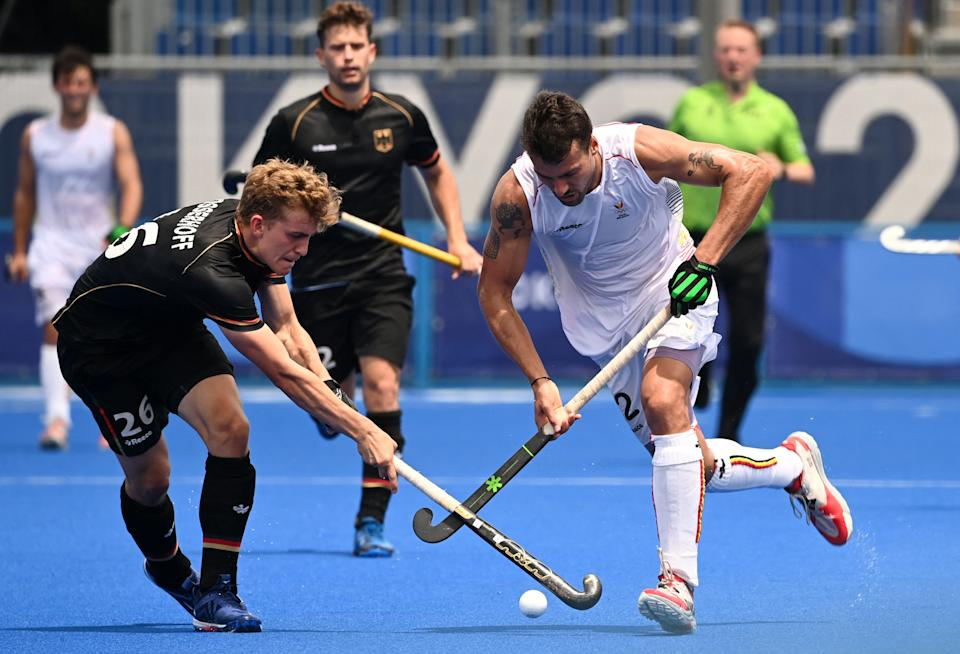 Belgium's Simon Pierre Gougnard (R) is tackled by Germany's Niklas Bosserhoff during their men's pool B match of the Tokyo 2020 Olympic Games field hockey competition, at the Oi Hockey Stadium in Tokyo on July 26, 2021. (Photo by Ina Fassbender / AFP) (Photo by INA FASSBENDER/AFP via Getty Images)