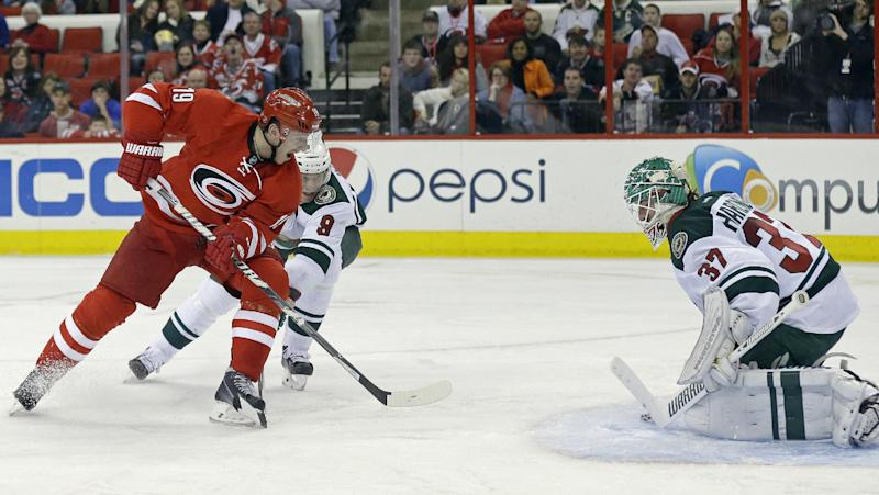 Carolina Hurricanes' Jiri Tlusty (19) scores on Minnesota Wild goalie Josh Harding (37) as Wild's Mikko Koivu (9), of Finland, defends during the second period of an NHL hockey game in Raleigh, N.C., Saturday, Nov. 9, 2013. (AP Photo/Gerry Broome)