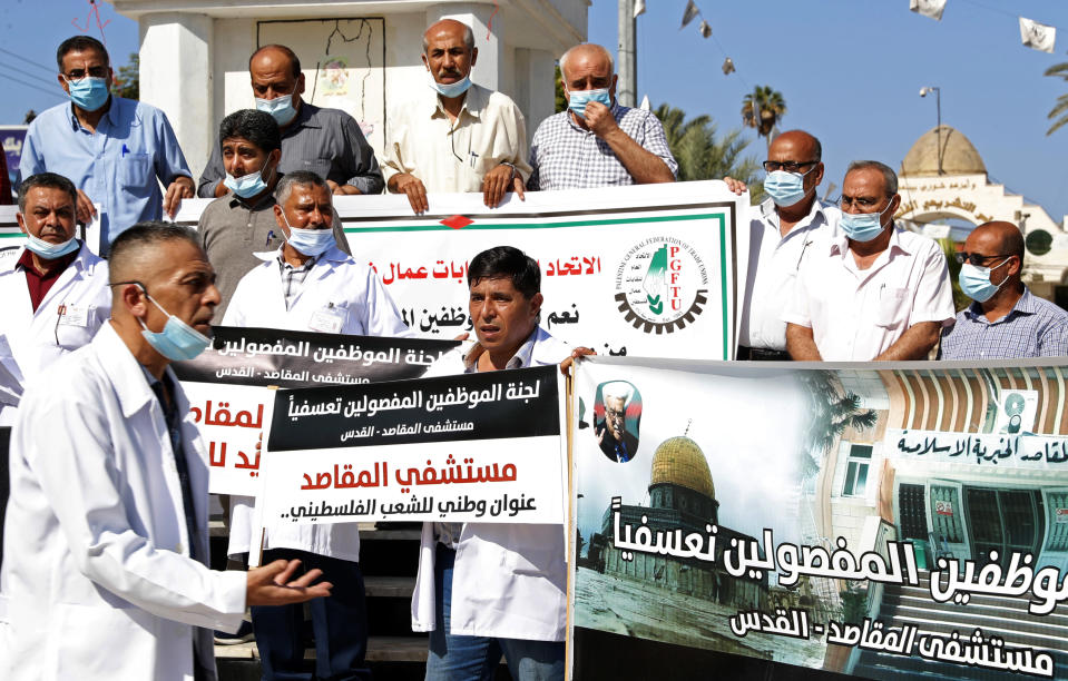 "Medical workers hold placards while staging a sit-in protest at the Unknown Soldier Square in Gaza City, Wednesday, Oct. 21, 2020. Arabic reads ""Makassed hospital is a national address for the Palestinian people."" ""The illegally fired employees from Makassed hospital."" Seven medical workers from the Gaza Strip said Wednesday an Israeli travel ban deprived them from getting to the east Jerusalem hospital where they worked for many years and the hospital eventually fired them. (AP Photo/Adel Hana)"