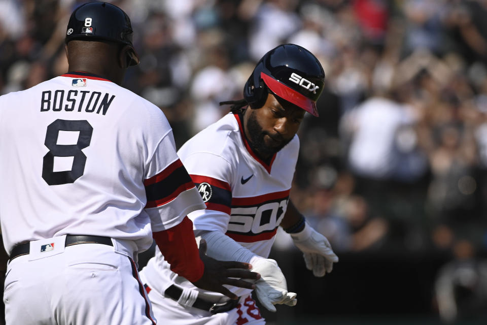 Chicago White Sox's Brian Goodwin, right, high-fives first base coach Daryl Boston (8) after hitting a walkoff home run during the ninth inning of a baseball game against the Cleveland Indians, Sunday, Aug. 1, 2021, in Chicago. (AP Photo/Matt Marton)
