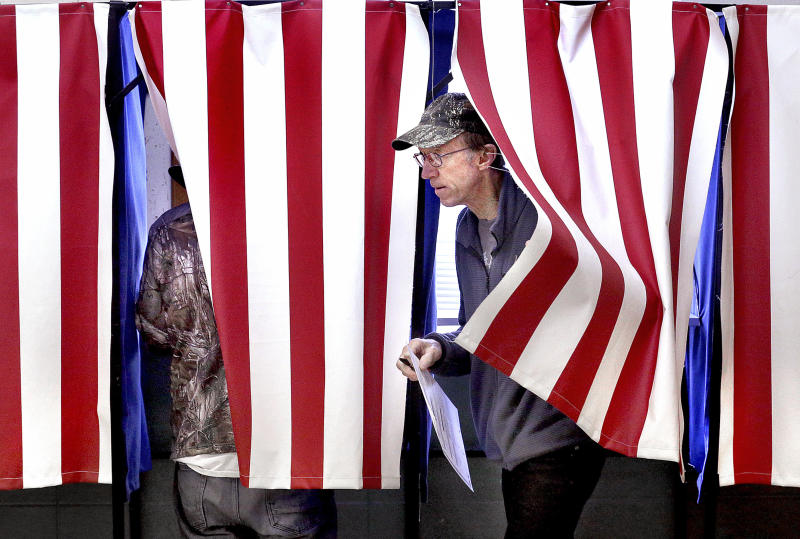 FILE - In this Nov. 6, 2018, file photo, Dan Chase steps out of a voting booth at Town of Hamilton Town Hall in West Salem, Wis. A judge's ruling to purge up to 234,000 voter registrations in swing state Wisconsin had Democrats vowing Monday, Dec. 16, 2019 to double down on efforts to make sure anyone kicked off the rolls is able to re-register before the 2020 presidential election.(Peter Thomson/La Crosse Tribune via AP, File)