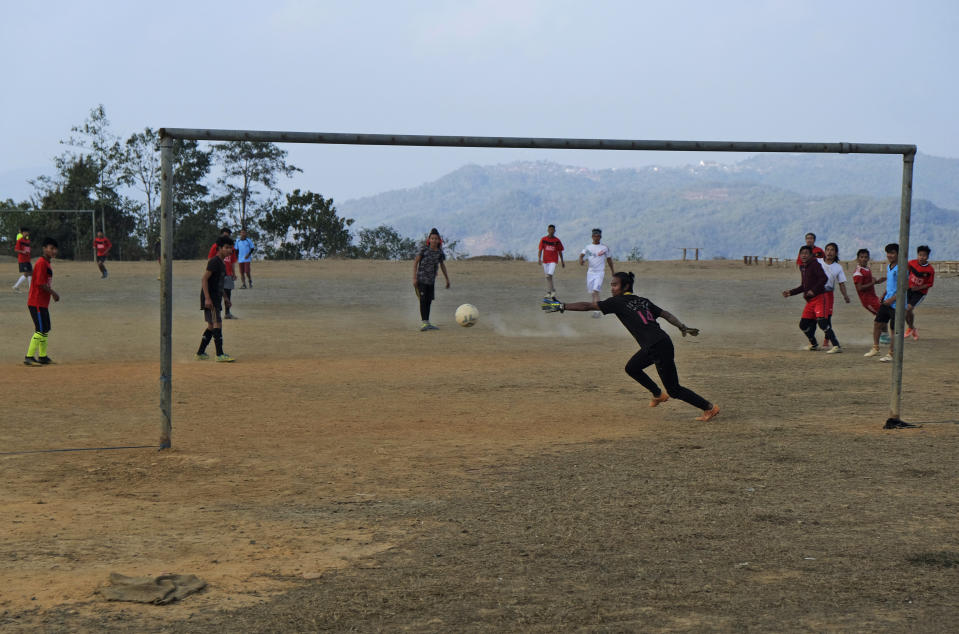The goalkeeper reaches for the ball during a friendly soccer match between villages in Shangshak, in the northeastern Indian state of Manipur, Saturday, Jan. 30 2021. Everyone who can play can get chosen for a match. The team from Shangshak village was herded together hurriedly in a day's notice. Most spent the hours before the match painting a house, a common practice in the community where the culture of helping hands remains deeply ingrained. (AP Photo/Yirmiyan Arthur)