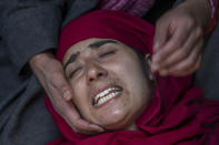 A Kashmiri woman wails outside a house allegedly ransacked by security forces after suspected militants killed a policeman, in Beerwah area, Indian controlled Kashmir, Friday, Feb. 19, 2021. Anti-India rebels in Indian-controlled Kashmir killed two police officers in an attack Friday in the disputed region's main city, officials said. Elsewhere in the Himalayan region, three suspected rebels and a policeman were killed in two gunbattles. (AP Photo/Dar Yasin)