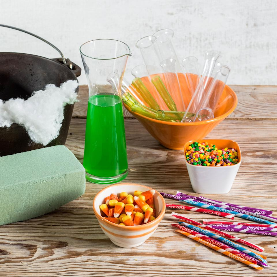 """<p>-Black cast iron pot (or other container of choice)<br /> -Plastic """"test tubes"""" found in the party section at craft stores<br /> -Green juice drink<br /> -Candy of choice<br /> -Florist picks (tops removed)<br /> -White """"spider web"""" netting found in Halloween/seasonal section of craft store<br /> -Florist foam (dry)</p>"""