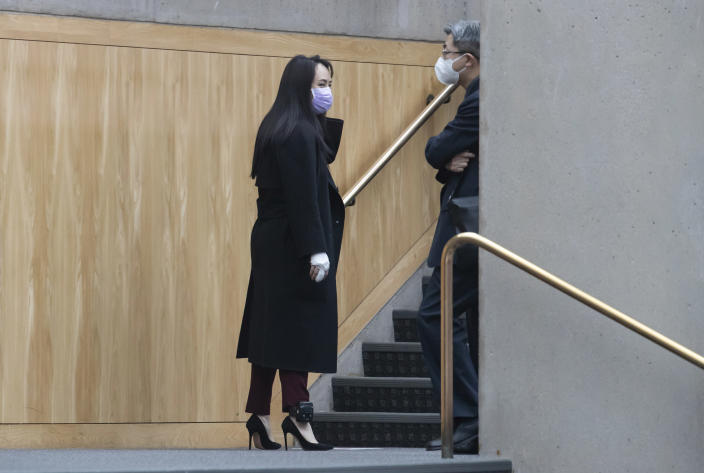 Chief Financial Officer of Huawei, Meng Wanzhou, left, is seen with a bandaged middle finger and hand during a break from a hearing at British Columbia Supreme Court, in Vancouver, British Columbia, Friday, March 19, 2021. (Darryl Dyck/The Canadian Press via AP)