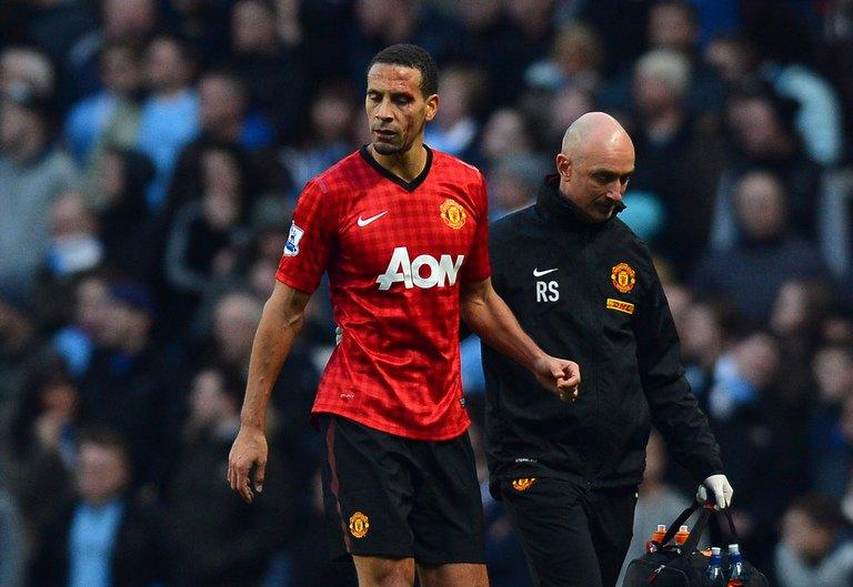 Manchester United's defender Rio Ferdinand (L) is helped from the pitch in Manchester on December 9, 2012