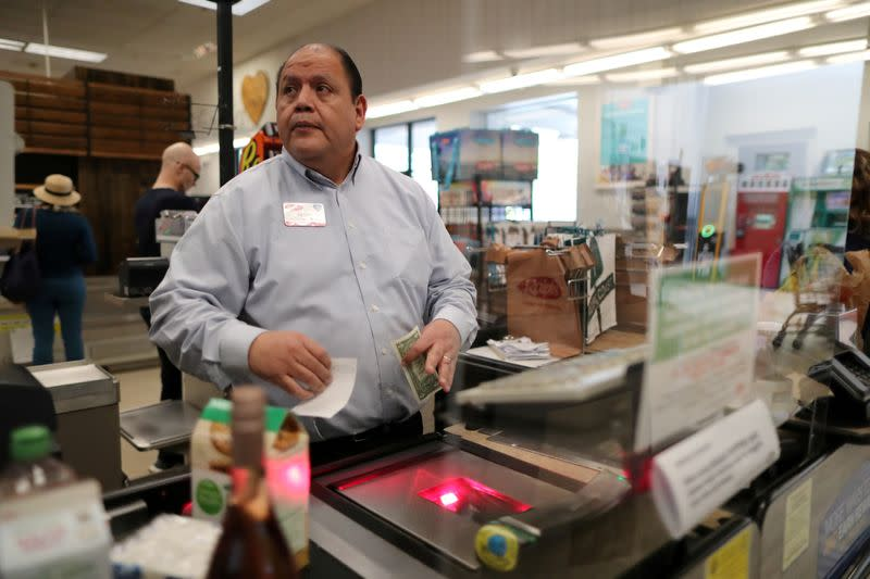 Assistant store manager Jesus Alvarez rings up groceries from behind a new plexiglass barrier at Ralphs Kroger grocery store after California issued a stay-at-home order in an effort to prevent the spread of coronavirus disease (COVID-19), in Los Angeles