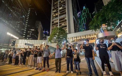 Demonstrators join hands to form a human chain during the Hong Kong Way event in the Central district of Hong Kong, China, on Friday - Credit: Bloomberg