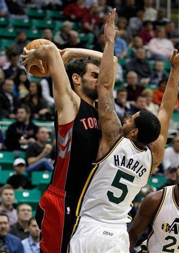 Toronto Raptors guard Jose Calderon, left, tries to get a pass off against the defense of Utah Jazz guard Devin Harris (5) during the first half of their NBA basketball game in Salt Lake City, Wednesday, Jan. 25, 2012. (AP Photo/Steve C. Wilson)