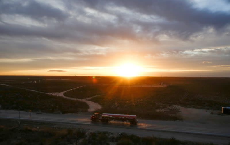 FILE PHOTO: The sun rises behind an oil tanker driving through the Permian Basin in Mentone