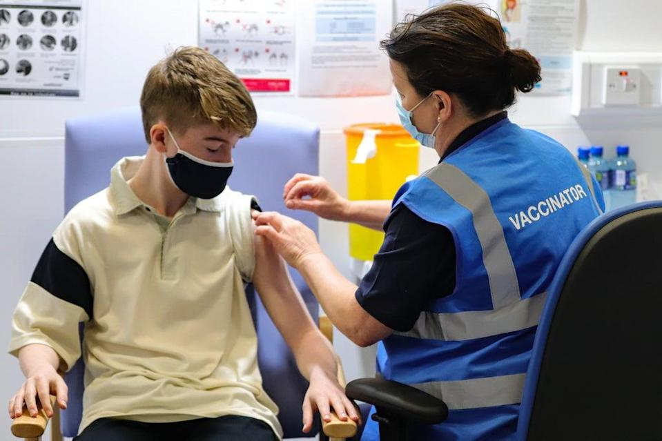 Kevin Mckeon, 14, receives his first dose of the Covid-19 vaccine at the Citywest vaccination centre in Dublin (PA)