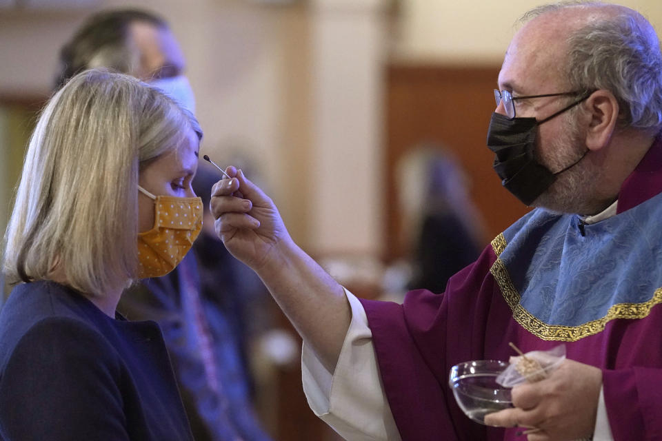 Catholic Priest Paul Soper, right, uses a swab out of concern for the coronavirus, to apply ash to the forehead of a parishioner during Ash Wednesday Mass at Saint Margaret Mary Parish, in Westwood, Mass., Wednesday, Feb. 17, 2021. (AP Photo/Steven Senne)