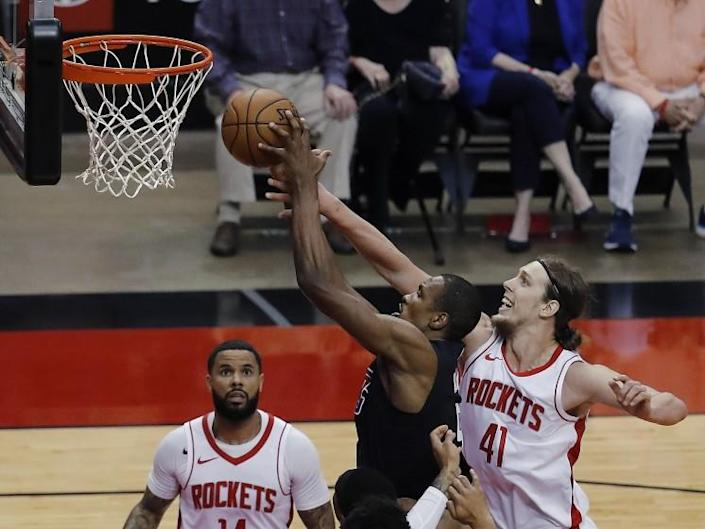 The Clippers' Serge Ibaka, middle, drives to the basket past the Rockets' Kelly Olynyk (41) on May 14, 2021, in Houston.