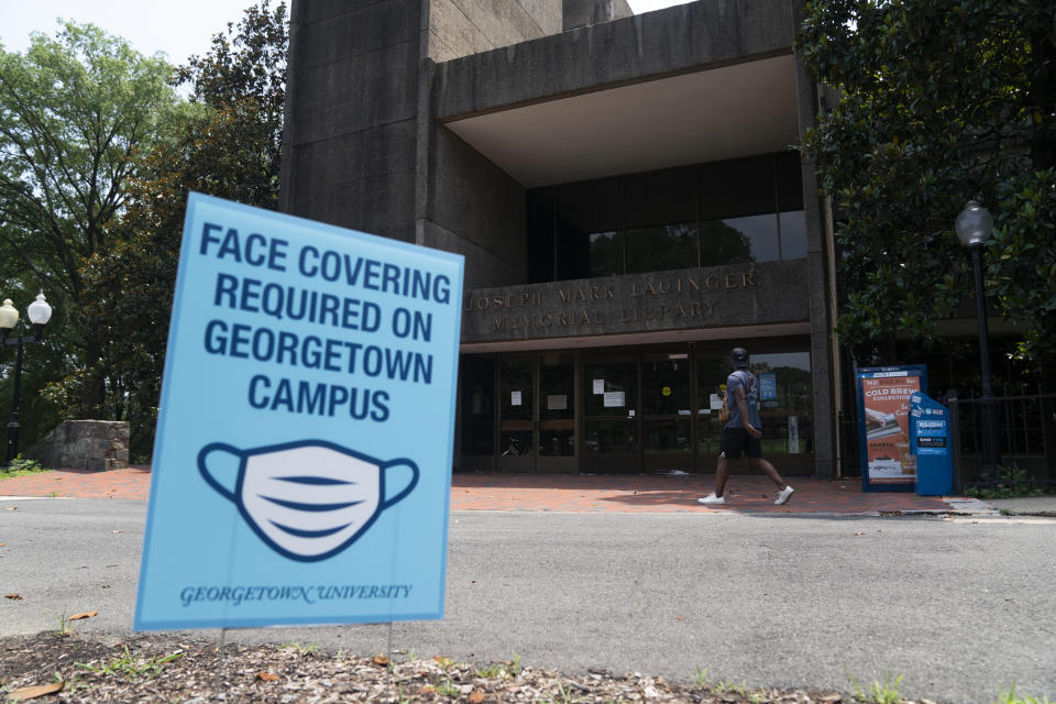 A sign reminding people to wear face masks is seen in front of a library on Georgetown University's main campus in Washington, D.C., the United States, July 7, 2020. (Photo: Xinhua/Liu Jie via Getty Images)