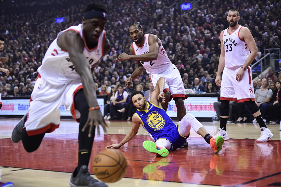 Golden State Warriors guard Stephen Curry (30) and Toronto Raptors forward Kawhi Leonard (2) and center Marc Gasol watch as Raptors forward Pascal Siakam (43) tracks down a loose ball during the first half of Game 1 of basketball's NBA Finals, Thursday, May 30, 2019, in Toronto. (Frank Gunn/The Canadian Press via AP)