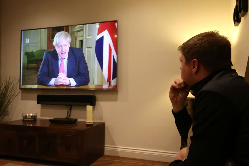 FILE PHOTO: A man watches British Prime Minister Boris Johnson's press conference as the spread of coronavirus disease (COVID-19) continues in Newcastle-under-Lyme