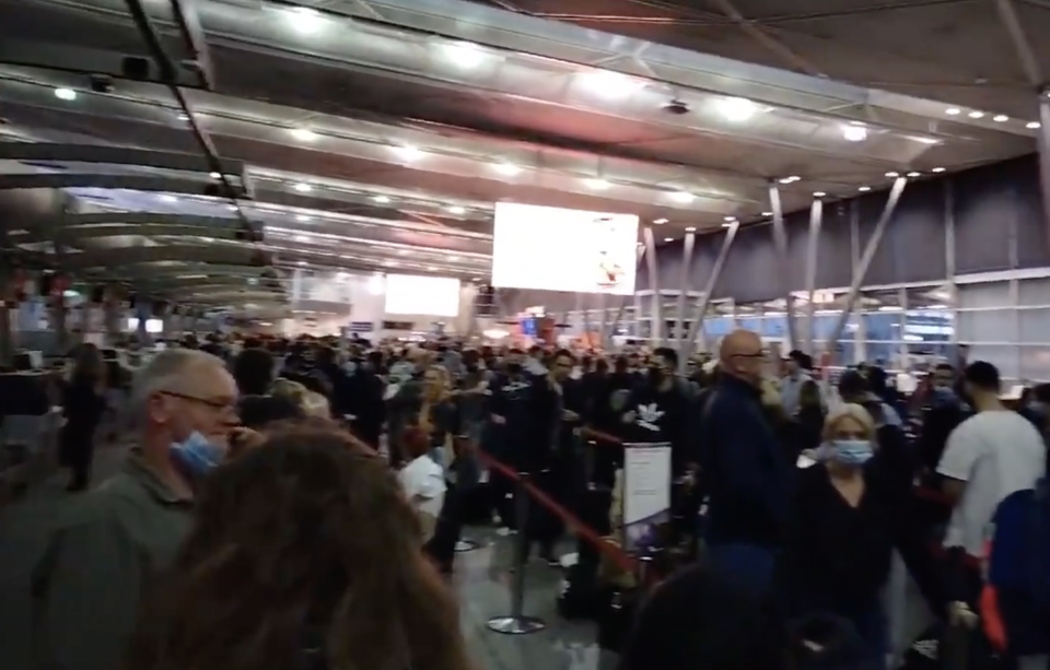 People lined up at a crowded airport due to delays caused by a Virgin Australia IT outage.