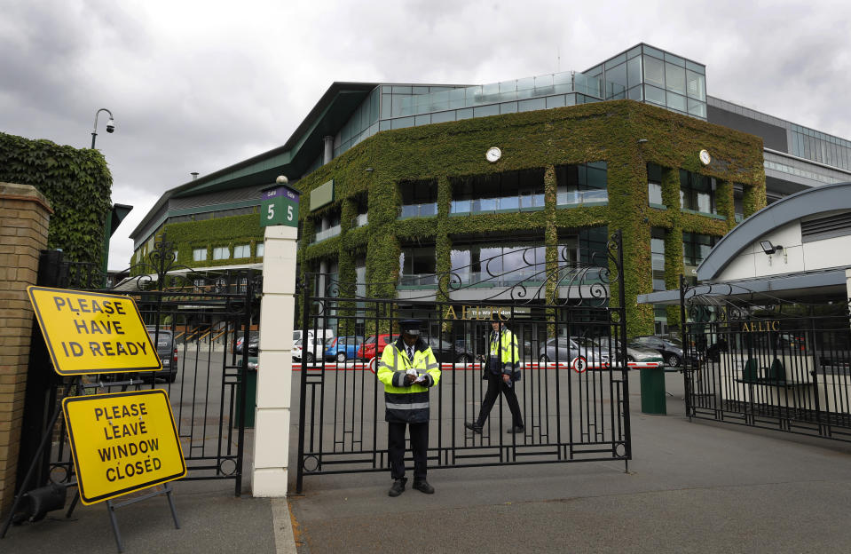 FILE - In this file photo dated Monday, June 29, 2020, security guards in front of the Centre Court at the All England Lawn Tennis Club, as the 2020 tennis championships are cancelled due to the coronavirus in Wimbledon, London. For all of the pandemic-related planning discussed for this year's return of Wimbledon — much still to be determined, including fan capacity and prize money — Tuesday's biggest news out of the All England Club takes effect in 2022: There will be play on the Grand Slam tournament's middle Sunday. (AP Photo/Kirsty Wigglesworth, FILE)