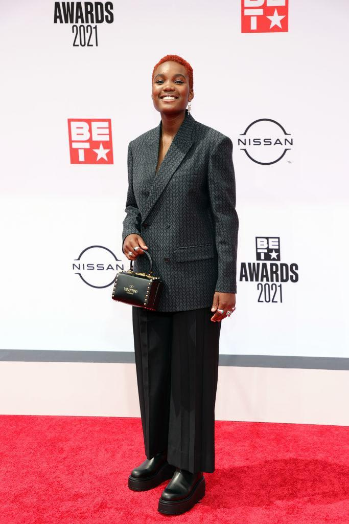 Arlo Parks attends the BET Awards 2021 in a pantsuit and small Valentino purse