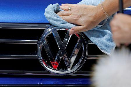 A worker shines the grill of a Volkswagen car displayed on media day at the Paris auto show. September 30, 2016. REUTERS/Benoit Tessier/Files