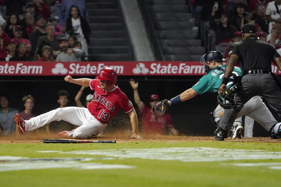 Los Angeles Angels' Phil Gosselin, left, scores under the tag of Seattle Mariners catcher Cal Raleigh on a double by Brandon Marsh during the fifth inning of a baseball game Saturday, Sept. 25, 2021, in Anaheim, Calif. (AP Photo/Mark J. Terrill)