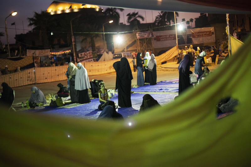 Supporters of Egypt's ousted President Mohammed Morsi gather before breaking their daylong Ramadan fast with the Iftar meal during a protest near Cairo University in Giza, Egypt, Monday, Aug. 5, 2013. More than a month after Morsi's ouster, thousands of the Islamist leader's supporters remain camped out in two key squares in Cairo demanding his reinstatement. Egypt's military-backed interim leadership has issued a string of warnings for them to disperse or security forces will move in, setting the stage for a potential violent showdown.(AP Photo/Manu Brabo)