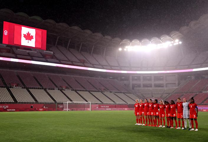 <p>Team Canada pauses for the national anthem prior to the women's Group E soccer match between Canada and Great Britain at Kashima Stadium.</p>