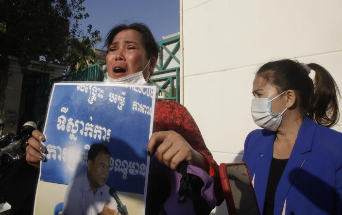 Prum Chenda, left, wife of a jailed former opposition activist, holds a portrait of her husband in front of the Phnom Penh Municipal Court, in Phnom Penh, Cambodia, Thursday, Jan. 14, 2021. The trial of more than 60 critics and opponents of the Cambodian government charged with treason and other offenses for taking part in nonviolent political activities resumed Thursday, with rights advocates skeptical that justice is being served. (AP Photo/Heng Sinith)
