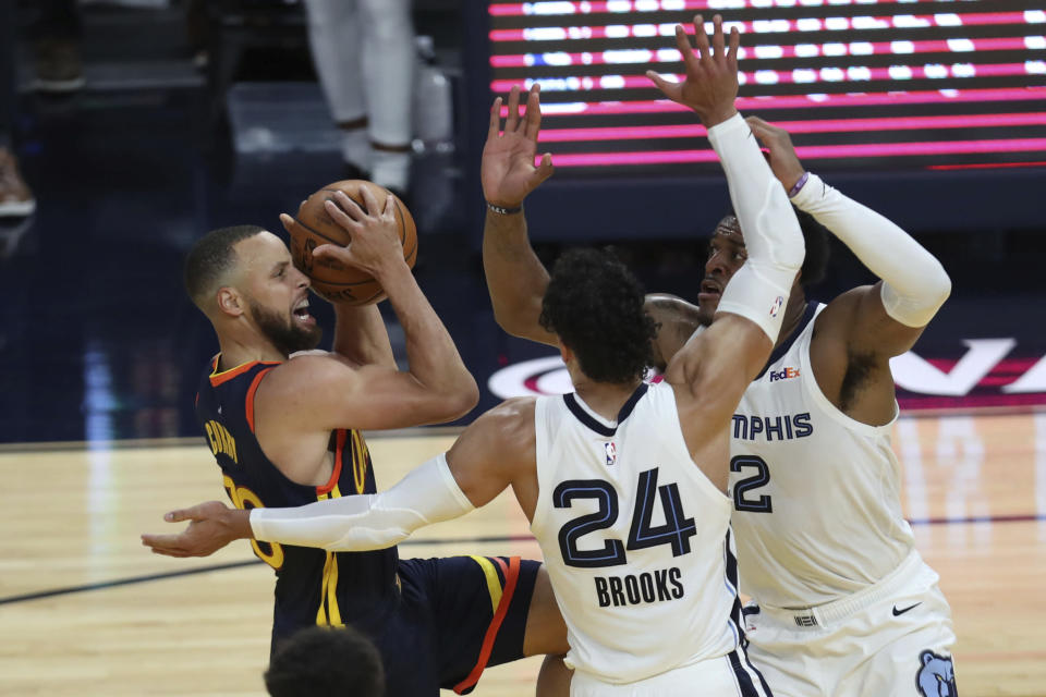Golden State Warriors' Stephen Curry, left, shoots against Memphis Grizzlies' Dillon Brooks, center, and Xavier Tillman Sr. during the first half of an NBA basketball Western Conference play-in game in San Francisco, Friday, May 21, 2021. (AP Photo/Jed Jacobsohn)