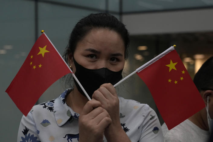 A supporter of Huawei CFO Meng Wanzhou holds up Chinese national flags at the Shenzhen Bao'an International Airport in Shenzhen in southern China's Guangdong Province, Saturday, Sept. 25, 2021. A top executive from global communications giant Huawei Technologies returned to China on Saturday following what amounted to a high-stakes prisoner swap with Canada and the U.S. (AP Photo/Ng Han Guan)