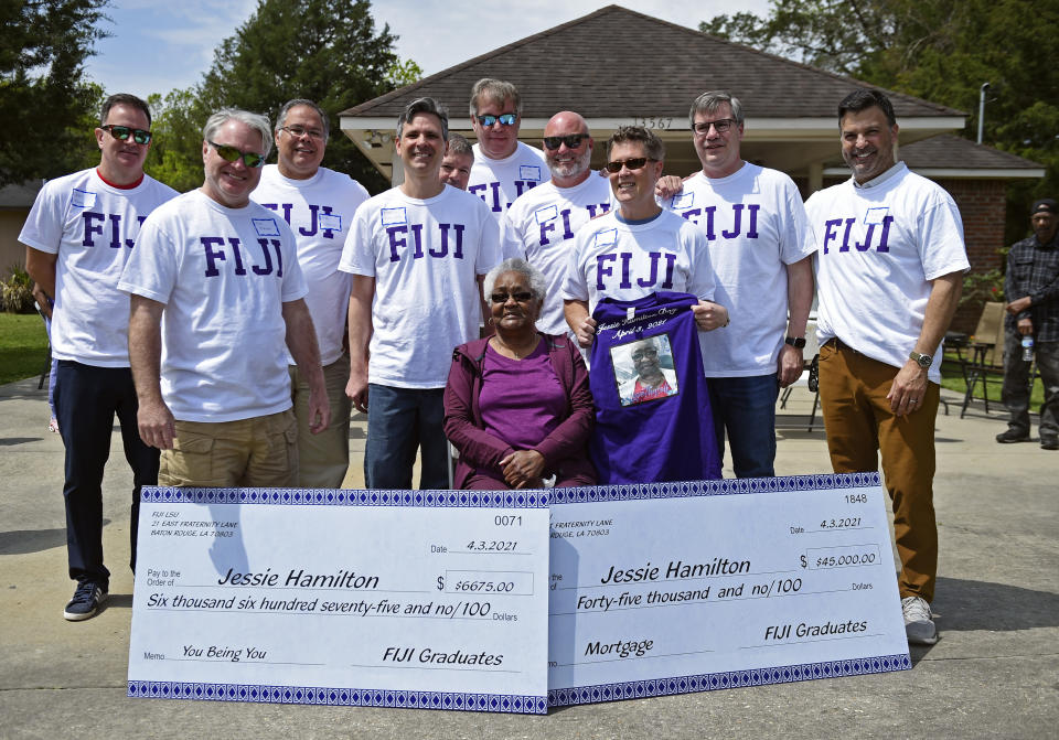 "Jessie Hamilton, seated, is surrounded by LSU FIJI graduates as they gathered to surprise their former house kitchen staff member, Saturday, April 3, 2021, and celebrate ""Jessie Hamilton Day"" in Baker, La. (Hilary Scheinuk/The Advocate via AP)"